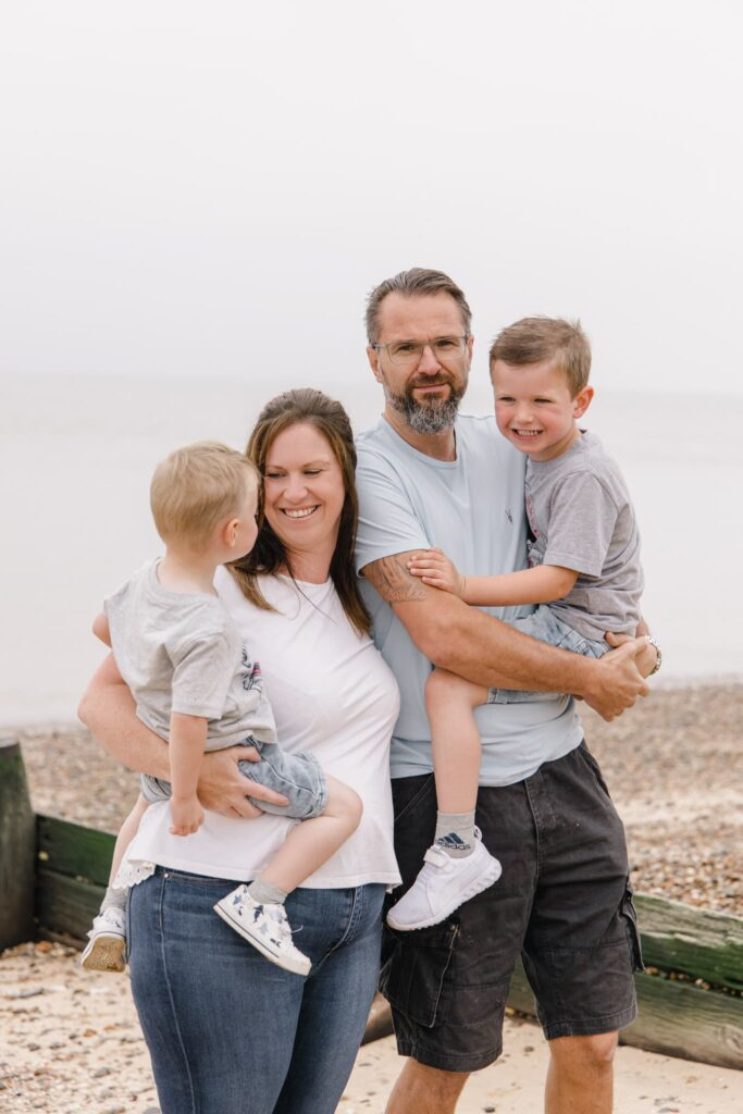 family on the beach in kent having their photo taken. Kids up in parents arms.
