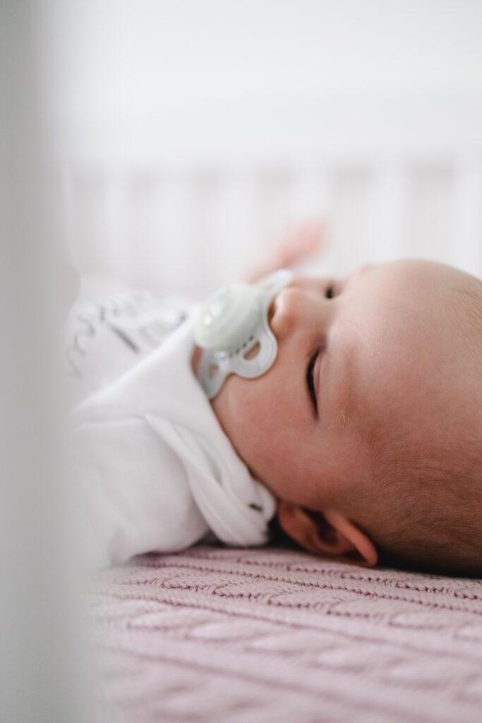 Sittingbourne newborn photoshoot. Newborn laying in her cot.